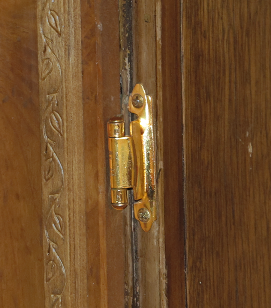 Close-up of a small cabinet hinge.