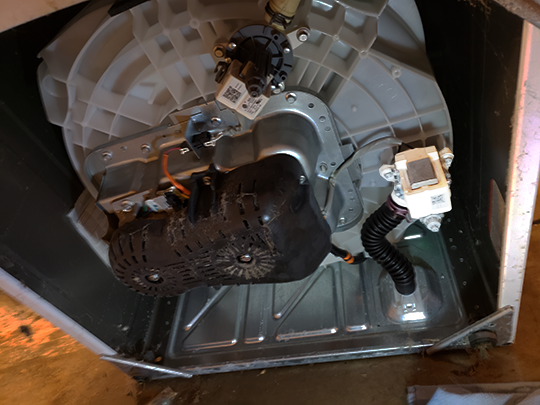 The drain pump on a recent GE washing machine is located on the bottom of the tub itself. Tilt the machine backwards to get to it.