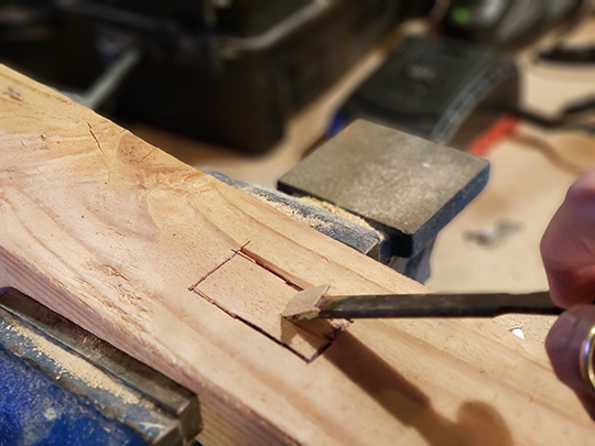 Drive the chisel at an angle to begin removing wood.