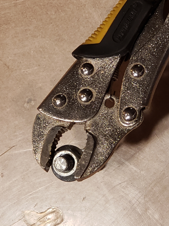 The flat jaws of the locking pliers firmly hold onto two of the nut's surfaces.