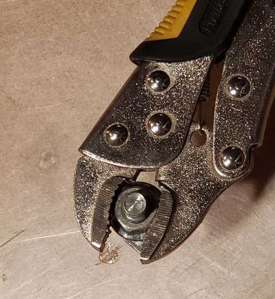 The serrated jaws of these locking pliers grab and hold onto at least two of the sides of this hex nut.