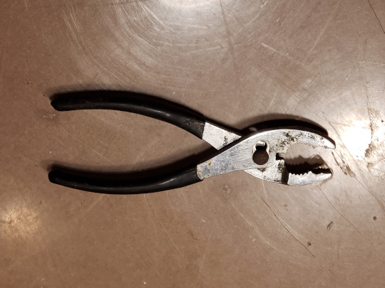 Slip joint pliers are really handy, but don't lock in place. Be3cause of that, you must readjust them every time you move them.